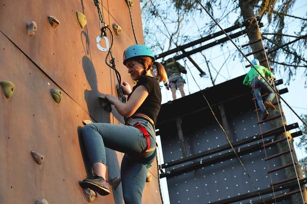 Jeune femme active sur la paroi rocheuse au centre sportif - à l'extérieur