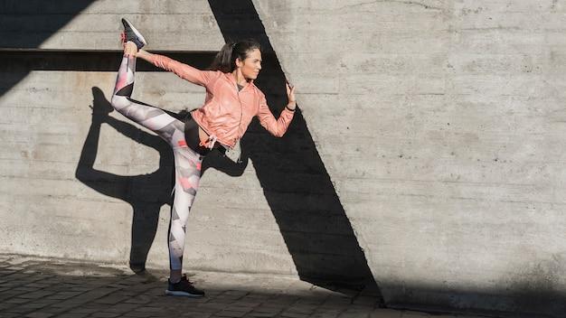 Jeune femme active qui s'étend en plein air