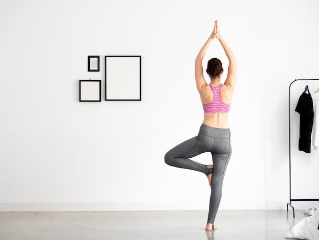 Jeune femme active en tenue sportive, faire des postures de yoga
