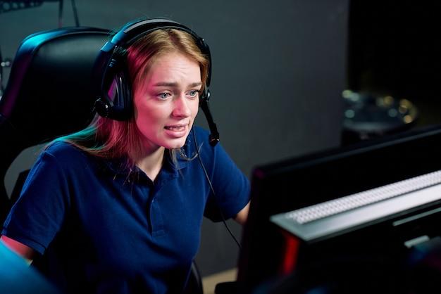 Jeune femme addict e-sport dans le casque en regardant l'écran de l'ordinateur pendant la compétition cyber alors qu'il était assis dans un club de jeu moderne