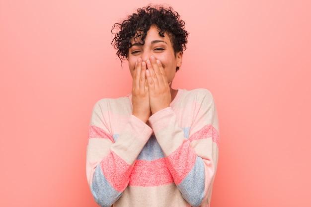 Jeune femme adolescente afro-américaine mixte rire de quelque chose, couvrant la bouche avec les mains.