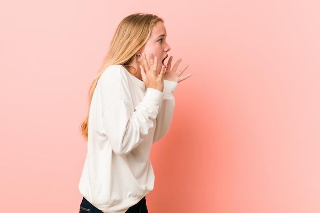 Jeune femme adolescente blonde crie fort, garde les yeux ouverts et les mains tendues.