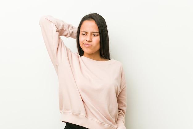 Jeune femme adolescente hispanique mignonne touchant l'arrière de la tête, pensant et faisant un choix.