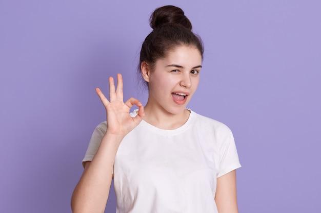 Jeune femme adorable aux cheveux noirs montrant signe ok avec les doigts, un clin d'œil avec son œil