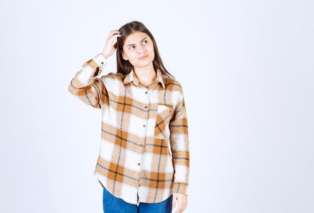 Jeune femme adorable dans des vêtements décontractés, debout sur un mur blanc.