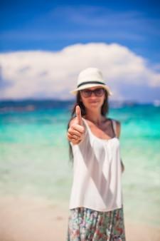 Jeune femme adorable, montrant les pouces vers le haut sur la plage blanche