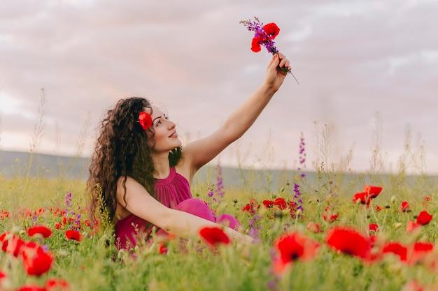 Jeune femme adorable portant du pavot dans ses cheveux et tenant un bouquet de fleurs sauvages