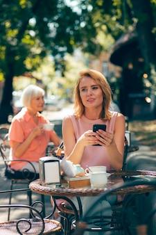 Jeune femme adulte assise dans un café avec un smartphone dans les mains et regardant loin avec un sourire
