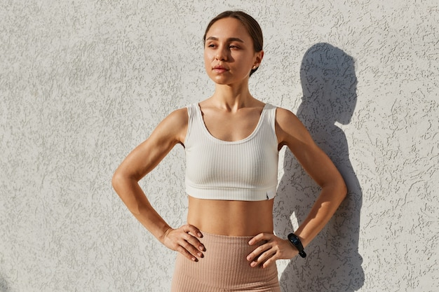 Jeune femme adulte aux cheveux noirs portant un haut sportif blanc debout près du mur à l'extérieur, regardant ailleurs, gardant les mains sur les hanches, a une expression confiante, posant après l'entraînement.