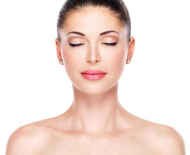 Jeune femme adulte avec beau visage - isolé sur blanc. concept de soins de la peau. closeup portrait avant d'une jeune fille adulte