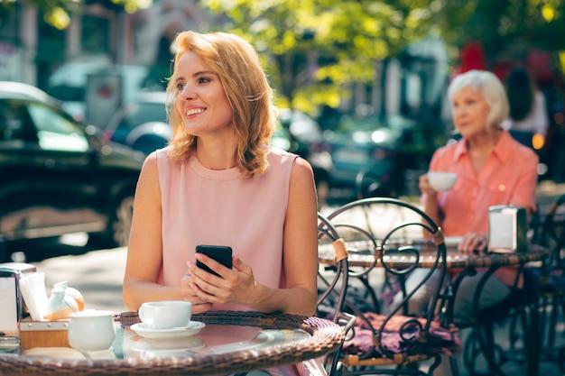 Jeune femme adulte calme assise avec un smartphone à la table du café et regardant au loin