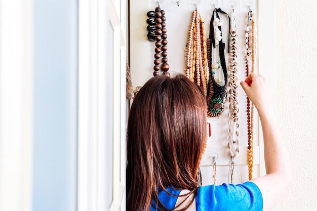 Jeune femme adulte commandant des colliers printemps-été. utilisation conceptuelle d'accessoires pour femmes. la mode des femmes
