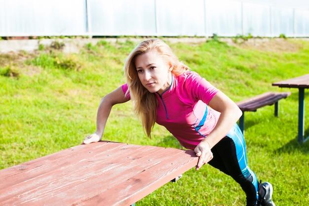 Une jeune femme adulte fait des exercices de gymnastique à l'extérieur. vie libre saine et sportive