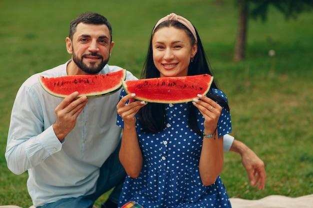 Jeune femme adulte et homme couple pique-nique au pré d'herbe verte dans le parc s'amusant et souriant avec pastèque