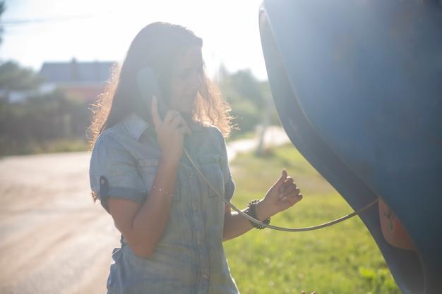 Jeune femme adulte parlant sur un téléphone public dans la rue dans un village russe au soleil