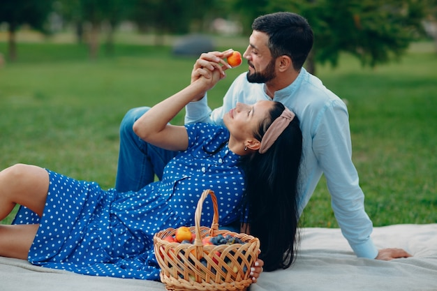Jeune femme adulte avec pêche à la main et homme couple pique-nique au pré d'herbe verte dans le parc.