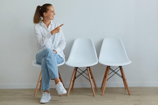 Jeune femme adulte portant une chemise blanche et un jean assis sur une chaise et pointant de côté avec l'index, détournant les yeux, ayant les cheveux noirs et la queue de cheval, étant de bonne humeur, exprimant des émotions positives.