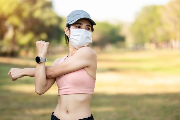 Jeune femme adulte portant un masque protecteur pendant l'étirement musculaire dans le parc en plein air