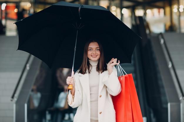 Jeune femme adulte positive portant des sacs à provisions en papier et un parapluie dans les mains