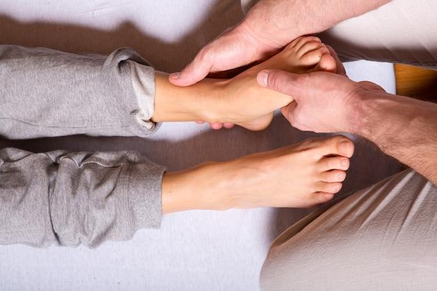 Une jeune femme adulte recevant un massage des pieds par un masseur masculin.