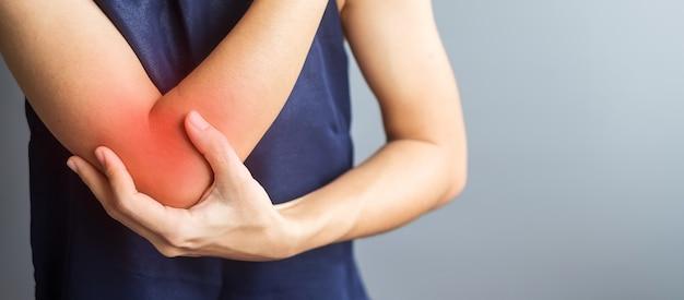 Jeune femme adulte avec ses douleurs musculaires sur fond gris. femme ayant mal au coude en raison d'une épicondylite latérale ou d'un tennis elbow. blessures et concept médical