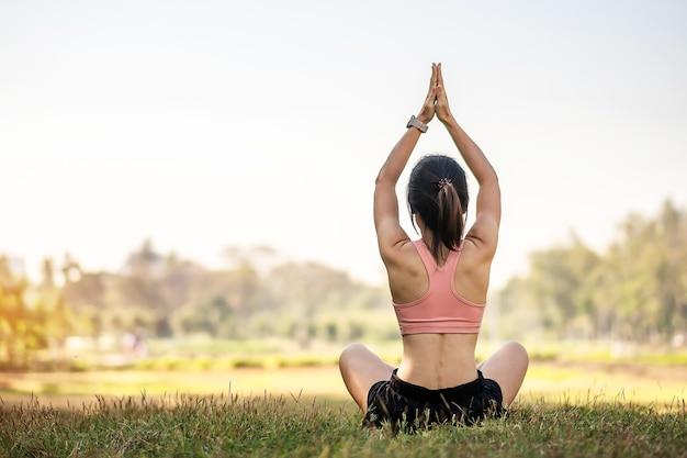 Jeune femme adulte en tenue de sport, faire du yoga dans le parc en plein air.