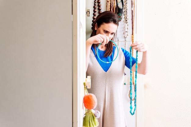 Jeune femme adulte vérifiant et commandant des colliers printemps-été à la maison dans une armoire. concept de commande à domicile