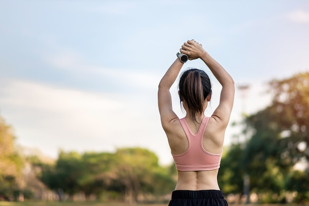 Jeune femme adulte en vêtements de sport rose qui s'étend du muscle dans le parc en plein air, femme sportive se réchauffe prête pour la course et le jogging le matin concepts de bien-être, de remise en forme, d'exercice et de conciliation travail-vie personnelle