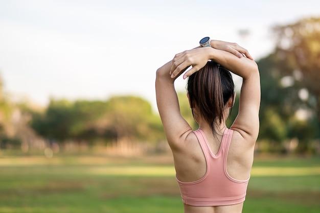 Jeune femme adulte en vêtements de sport rose qui s'étend de muscle dans le parc en plein air.