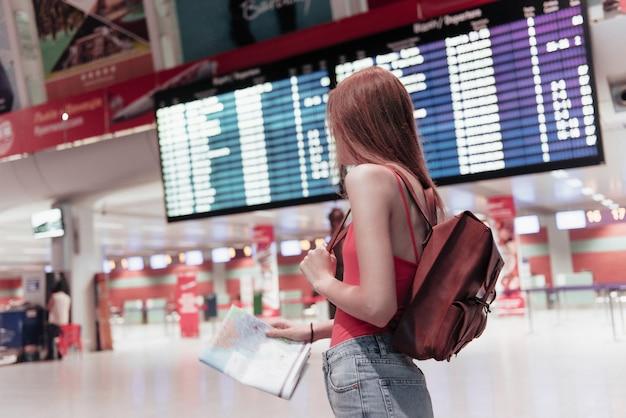 Jeune femme à l'aéroport avec carte en mains et panneau d'information sur l'arrière-plan regarde sur le côté
