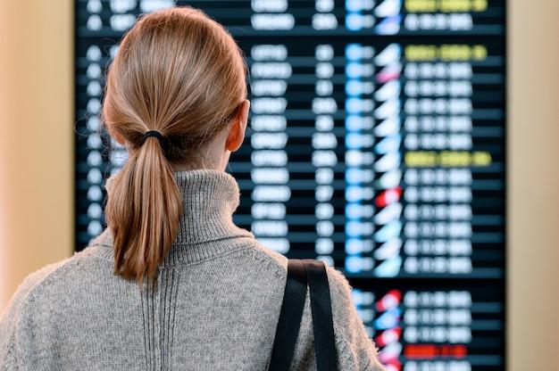 Jeune femme à l'aéroport international en regardant le panneau d'information de vol