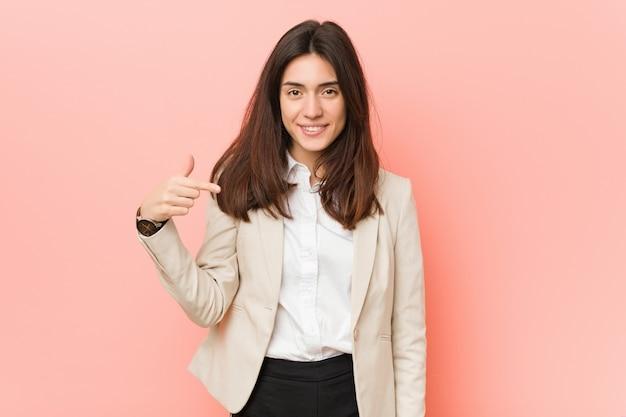 Jeune femme d'affaire brune contre-femme pointant en chemise, fier et confiante