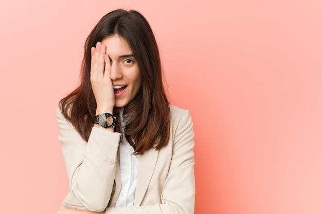 Jeune femme d'affaire brune contre rose s'amuser couvrant la moitié du visage avec palme.