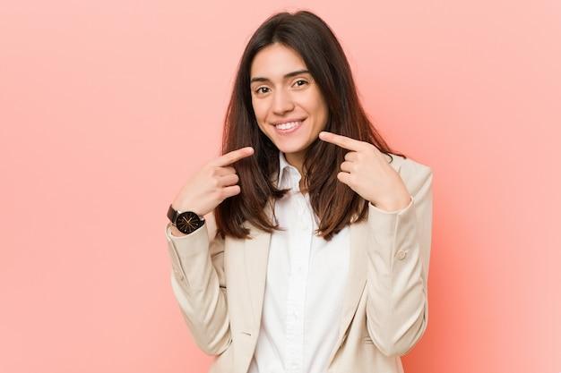 Jeune femme d'affaire brune sur des sourires roses, pointer du doigt la bouche.