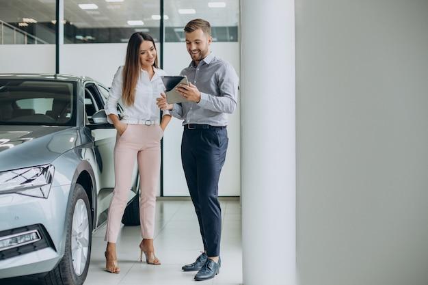 Jeune femme d'affaires achetant une voiture dans la salle d'exposition de voiture
