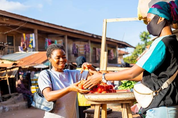 Jeune femme d'affaires africaine noire portant un masque facial faisant du shopping sur un marché africain local