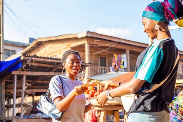 Jeune femme d'affaires africaine noire portant un masque facial faisant du shopping en payant la facture en espèces