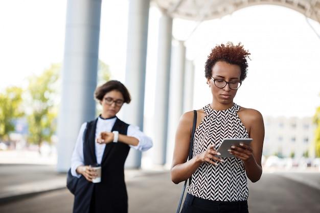 Jeune femme d'affaires africaine réussie regardant tablette sur centre d'affaires.