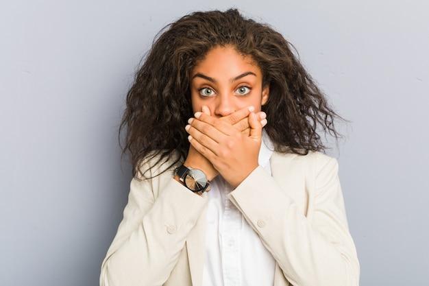 Jeune femme d'affaires afro-américaine choqué couvrant la bouche avec les mains.
