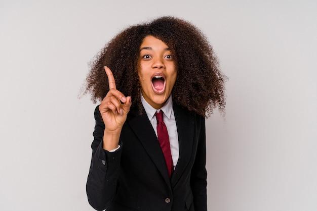 Jeune femme d'affaires afro-américaine portant un costume isolé sur blanc ayant une idée, concept d'inspiration.