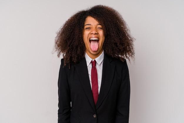 Jeune femme d'affaires afro-américaine portant un costume isolé sur blanc drôle et sympathique qui sort la langue.
