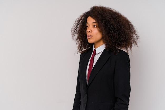 Jeune femme d'affaires afro-américaine portant un costume isolé sur blanc regardant à gauche, pose latérale.