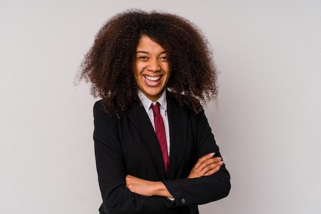 Jeune femme d'affaires afro-américaine portant un costume isolé sur blanc en riant et en s'amusant.