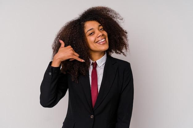Jeune femme d'affaires afro-américaine portant un costume isolé sur fond blanc montrant un geste d'appel de téléphone portable avec les doigts.
