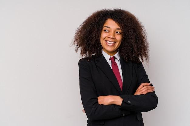 Jeune femme d'affaires afro-américaine portant un costume isolé sur fond blanc souriant confiant avec les bras croisés.