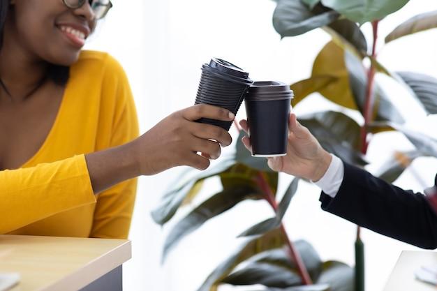Une jeune femme d'affaires afro-américaine séduisante portant un masque protecteur empêche le virus covid-19 de boire du café noir