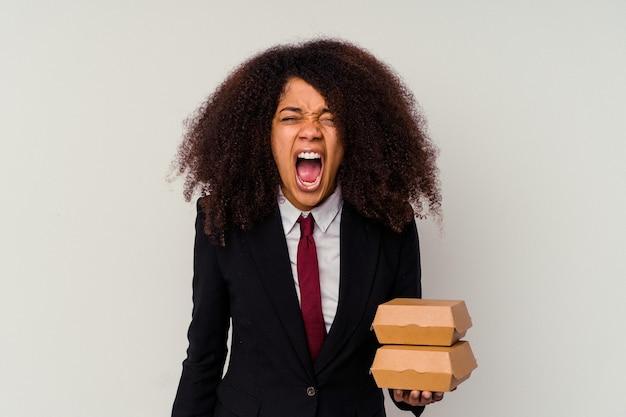 Jeune femme d'affaires afro-américaine tenant un hamburger isolé sur fond blanc criant très en colère et agressif.