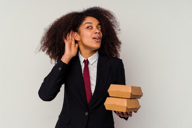 Jeune femme d'affaires afro-américaine tenant un hamburger isolé sur fond blanc en essayant d'écouter un commérage.