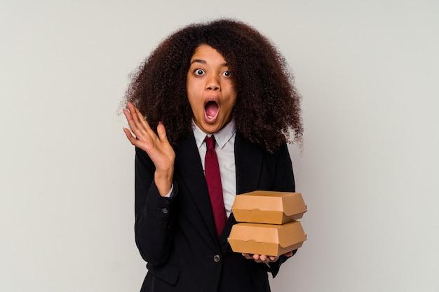 Jeune femme d'affaires afro-américaine tenant un hamburger isolé sur fond blanc surpris et choqué.