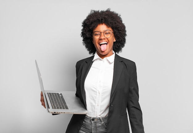 Jeune femme d'affaires afro avec une attitude joyeuse, insouciante et rebelle, plaisantant et tirant la langue, s'amusant. concept d'entreprise